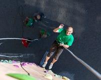 Lächelnder Mann, der auf Seil von der Spitze des Kletterwands absteigt stockfotos