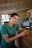 Lächelnder Mann, der bei der Anwendung des Telefons an der Stange weg schaut Stockbild