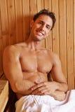 Lächelnder Mann, der in der Sauna sitzt Stockbild