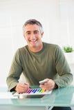Lächelnder Mann, der Diagramm und das Halten des Handys analysiert Stockbild