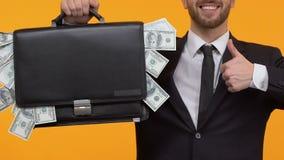 Lächelnder Mann, der die Daumen-oben halten vollen Aktenkoffer Geld, Startgewinn zeigt stock footage