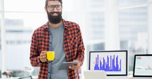 Lächelnder Mann, der digitale Tablette beim Haben des Tasse Kaffees im Büro verwendet Stockbild