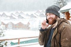Lächelnder Mann, der draußen am Handy im Schneewetter spricht Stockfotos