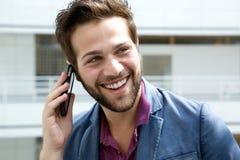 Lächelnder Mann, der durch Handy nennt Stockfotos