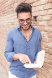 Lächelnder Mann, der ein Buch und Punkte zu ihm liest Lizenzfreie Stockfotografie
