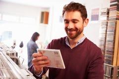 Lächelnder Mann, der eine CD in einem Rekordshop betrachtet Lizenzfreie Stockfotos