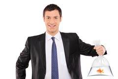 Lächelnder Mann, der eine Plastiktasche mit goldenen Fischen anhält Lizenzfreies Stockbild
