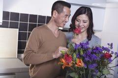 Lächelnder Mann, der eine Rose und eine Frau es vor einem bunten Blumenstrauß von Blumen in der Küche riechend hält Stockbilder