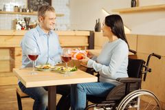 Lächelnder Mann, der einer behinderten Frau ein Geschenk gibt Stockfoto