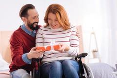 Lächelnder Mann, der einer glücklichen behinderten Frau ein Geschenk gibt Lizenzfreies Stockfoto