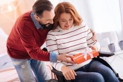 Lächelnder Mann, der einer verkrüppelten Frau ein Geschenk gibt Lizenzfreies Stockbild
