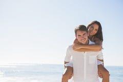 Lächelnder Mann, der Freundin ein Doppelpol betrachtet Kamera gibt Stockfotografie