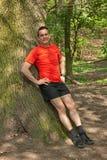 Lächelnder Mann, der gegen einen Baum trainiert und sich entspannt lizenzfreies stockbild
