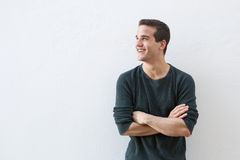 Lächelnder Mann, der gegen weißen Hintergrund mit den Armen gekreuzt steht Stockbild