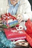 Lächelnder Mann, der Geschenke einwickelt Stockfotografie