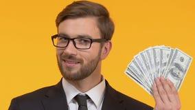 Lächelnder Mann, der in der Hand Bargeld, Vergünstigungen und Prämien, lokalisierten hellen Hintergrund hält stock video