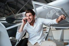 Lächelnder Mann, der am Handy in den kleinen Flugzeugen spricht Stockfoto