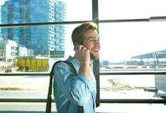 Lächelnder Mann, der am Handy am Flughafen geht und spricht Stockfoto