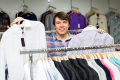 Lächelnder Mann, der Hemden im Mall wählt Lizenzfreie Stockbilder