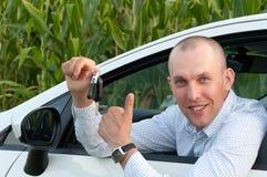 Lächelnder Mann, der im Auto sitzt Stockbild