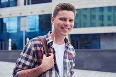 Lächelnder Mann, der Kamera beim Gehen in das Stadtzentrum mit betrachtet Stockfotografie
