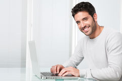 Lächelnder Mann, der an Laptop arbeitet Stockbild