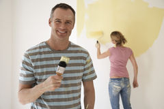 Lächelnder Mann, der Malerpinsel hält, während Frau Wand mit Rolle malt stockbilder