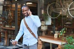 Lächelnder Mann, der mit einem Fahrrad spricht auf einem Mobiltelefon steht Lizenzfreie Stockfotos