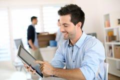 Lächelnder Mann, der mit einer digitalen Tablette arbeitet Lizenzfreie Stockbilder