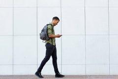 Lächelnder Mann, der mit intelligentem Telefon und Kopfhörern des Rucksacks geht Lizenzfreies Stockfoto