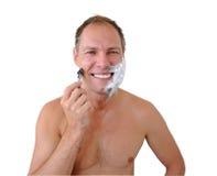 Lächelnder Mann, der mit Rasiermesser und Schaumgummi sich rasiert lizenzfreies stockbild