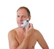 Lächelnder Mann, der mit Rasiermesser und Schaumgummi sich rasiert stockfoto
