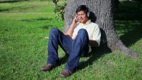 Lächelnder Mann, der Musik beim Sitzen gegen einen Baum hört stock video