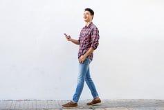 Lächelnder Mann, der Musik am Handy geht und hört Stockbild