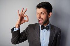 Lächelnder Mann, der okayzeichen blinzelt und zeigt Lizenzfreies Stockbild