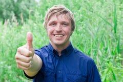 Lächelnder Mann, der sich Daumen zeigt Stockfotografie