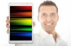 Lächelnder Mann, der Tablette auf Weiß hält stockbilder