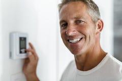 Lächelnder Mann, der Thermostat auf Hausheizungs-Heizsystem justiert stockbild