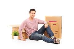 Lächelnder Mann, der vom Bewegen in ein neues Haus stillsteht Stockbild