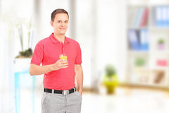 Lächelnder Mann, der zu Hause mit einem Glas Orangensaft aufwirft Stockbild