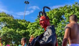Lächelnder Mann in einem Kostüm des Teufels mit rotem Gesicht, schwärzen Hörner und Mantel gehend auf Stelzen bei Bloco Orquestra Lizenzfreies Stockbild