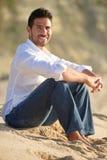 Lächelnder Mann gesetzt auf dem Sand Stockfoto
