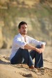 Lächelnder Mann gesetzt auf dem Sand Lizenzfreies Stockbild