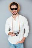 Lächelnder Mann im Hut und in der Sonnenbrille mit alter Weinlesekamera Stockbild