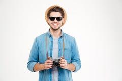 Lächelnder Mann im Hut und in der Sonnenbrille unter Verwendung der alten Fotokamera Stockfoto
