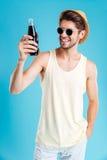 Lächelnder Mann im Hut und in Sonnenbrille, die Flasche Soda halten stockfotos