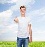 Lächelnder Mann im weißen T-Shirt, das sich Daumen zeigt Lizenzfreies Stockfoto