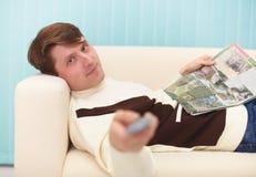 Lächelnder Mann, liegend auf Couch mit Zeitschrift Stockfoto