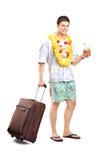 Lächelnder Mann mit dem Cocktail, das sein Gepäck trägt Stockfotos