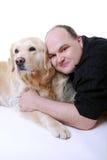 Lächelnder Mann mit goldenem Apportierhund Stockbild